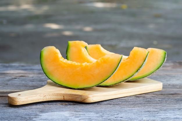 Geschnittene frische süße melone auf hölzernem brett. süße frucht.