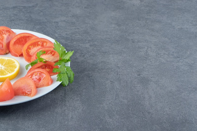 Geschnittene frische tomaten und petersilie auf weißem teller.