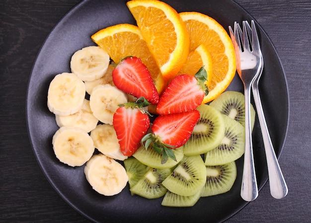 Geschnittene frucht (erdbeeren, kiwi, orange, banane) auf einem schwarzblech