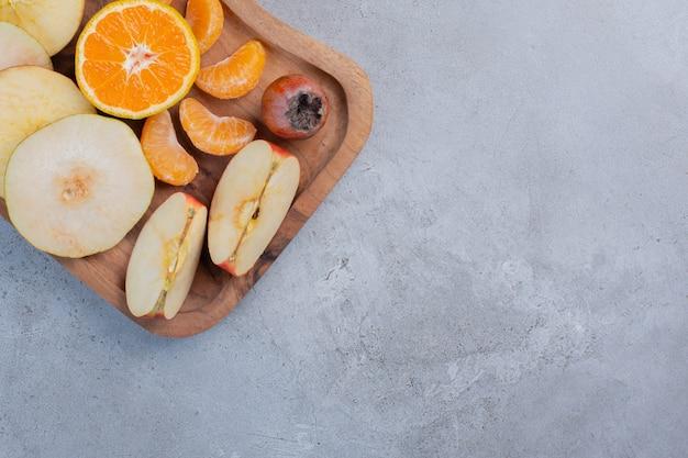 Geschnittene früchte gebündelt auf einem holzbrett auf marmorhintergrund.