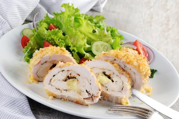 Geschnittene gebackene hühnerrolle in paniermehl mit parmesan gefüllt mit käse mit kräutern