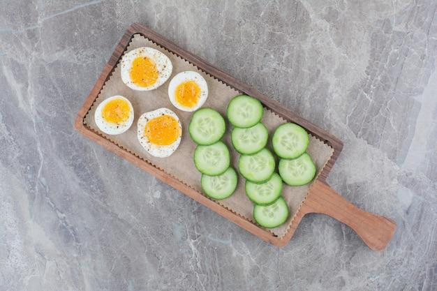 Geschnittene gekochte eier mit gurke auf holzbrett. foto in hoher qualität