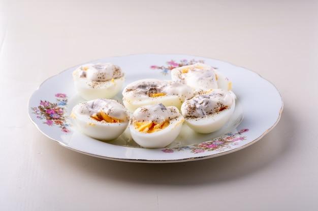 Geschnittene gekochte eier mit mayonnaise und pfeffer in der isolierten winkelansicht der weißen platte