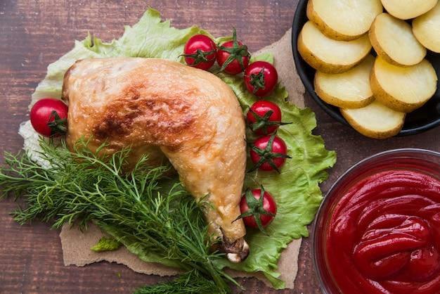 Geschnittene gekochte kartoffeln; gebratene hühnerkeule; soße; kirschtomate; dill zum abendessen auf salatblatt über holztisch