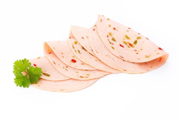 Geschnittene gekochte schinkenwurst lokalisiert auf weißem raum, draufsicht.