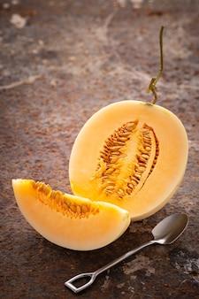 Geschnittene gelbe cantaloupe-melone mit dessertlöffel auf rostigem texturhintergrund