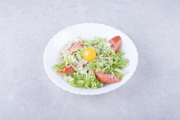 Geschnittene geräucherte würste, salat und eigelb in weißer schüssel.