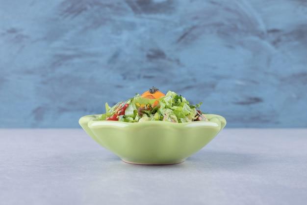 Geschnittene geräucherte würste, salat und tomate in grüner schüssel.