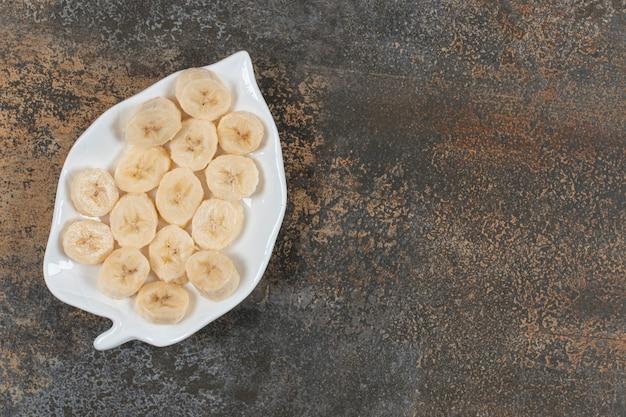 Geschnittene geschälte bananen auf weißem teller.