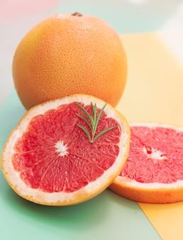 Geschnittene grapefruit auf farbigem hintergrund, verschwommenes licht herum