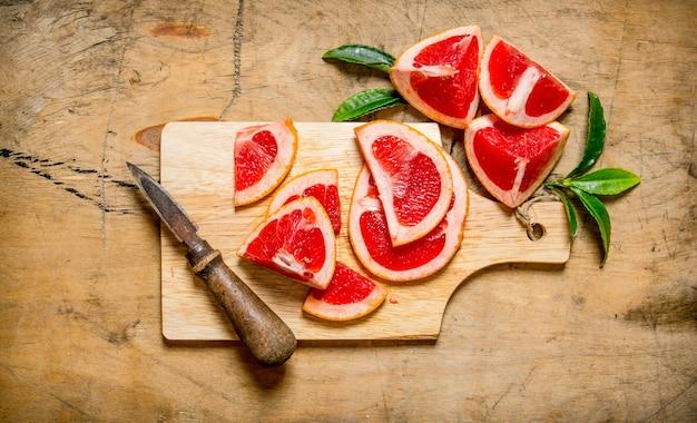 Geschnittene grapefruit auf holzbrett mit blättern auf holztisch. draufsicht