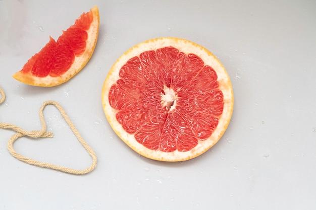 Geschnittene grapefruit mit rotem fruchtfleisch auf den hintergrund gelegt, verschwommenes licht herum