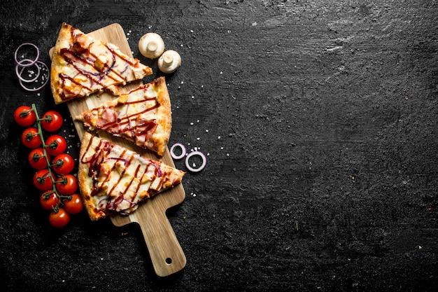 Geschnittene grillpizza mit tomaten auf zweig auf schwarzem holztisch