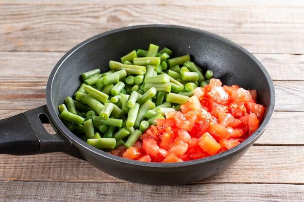 Geschnittene grüne bohnen und potamas in einer pfanne zum kochen von lobio aus grünen bohnen mit gemüse und tomaten. schritt für schritt rezept