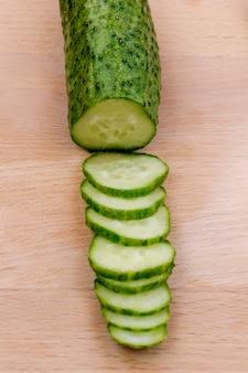 Geschnittene grüne gurke auf schneidebrett. draufsicht