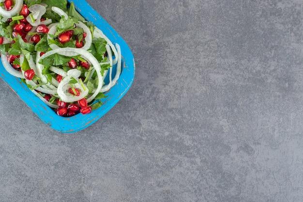 Geschnittene grüns, zwiebeln und granatapfelkerne auf blauem teller. foto in hoher qualität