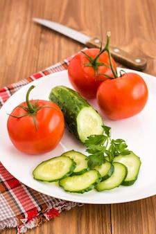 Geschnittene gurke und tomaten auf einer platte auf einem holztisch