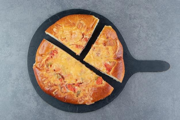 Geschnittene hausgemachte pizza auf schwarzem schneidebrett.