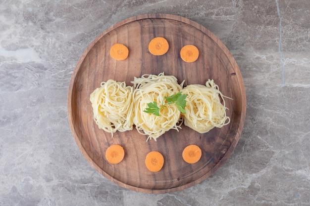 Geschnittene karotte neben grüns auf spaghetti, auf der holzplatte, auf dem marmor.