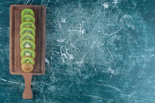 Geschnittene kiwi auf dem schneidebrett, auf dem marmortisch.