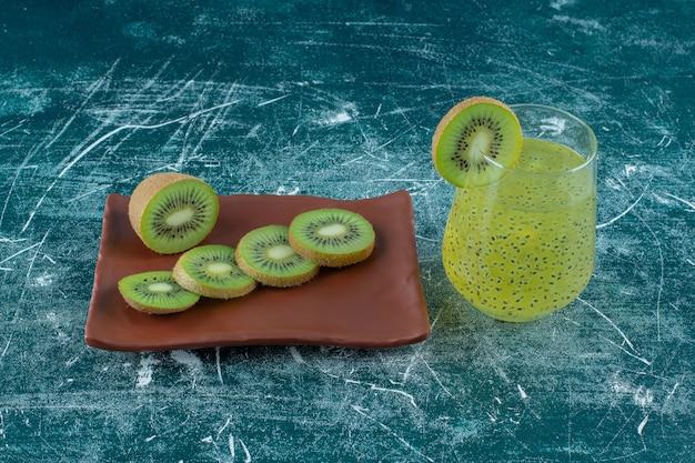 Geschnittene kiwi auf einem braunen teller neben einem glas kiwi-smoothie auf dem marmortisch.