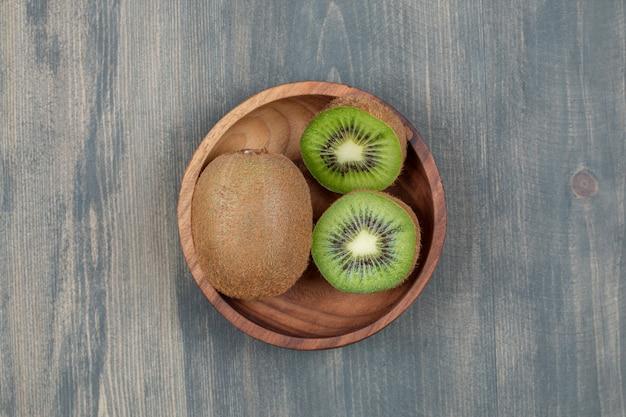 Geschnittene kiwi mit ganzer kiwi auf einem holztisch