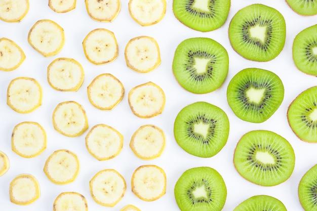 Geschnittene kiwi und banane getrennt auf weiß