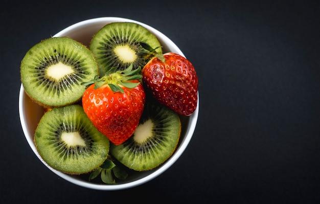Geschnittene kiwis und erdbeeren in einer weißen schüssel auf schwarz