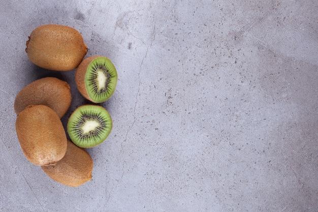 Geschnittene köstliche kiwi mit blättern, die auf steinhintergrund gelegt werden.