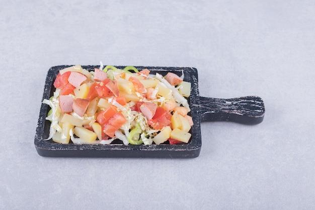 Geschnittene leckere würstchen mit frischem salat auf schwarzem brett.