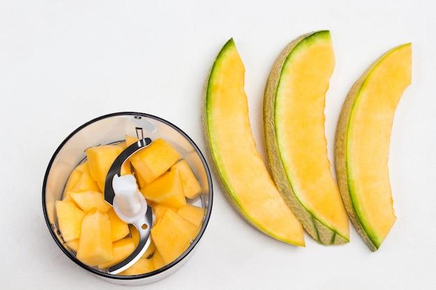 Geschnittene melone auf dem tisch. melone im mixbecher in stücke schneiden. weißer hintergrund. flach liegen
