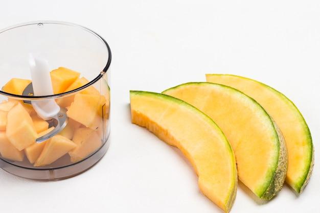 Geschnittene melone auf dem tisch. melone im mixbecher in stücke schneiden.