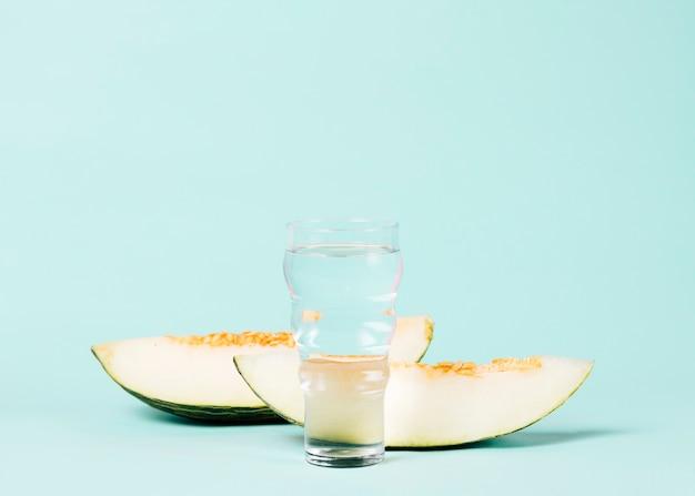 Geschnittene melone mit glas wasser