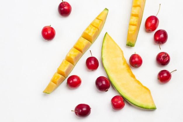 Geschnittene melone und kleine rote äpfel auf dem tisch. weißer hintergrund. flach liegen. speicherplatz kopieren