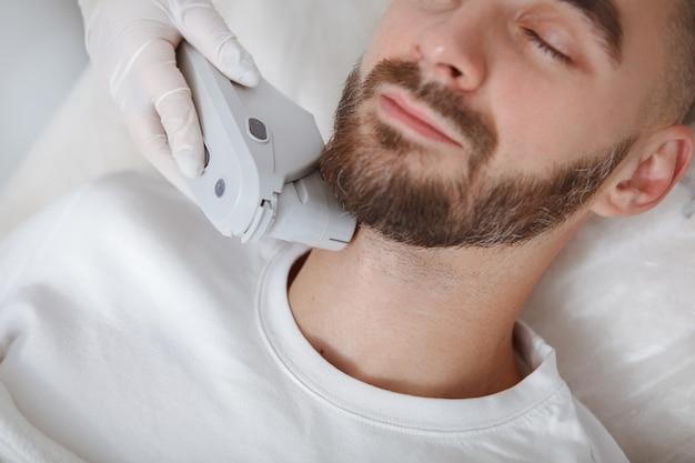 Geschnittene nahaufnahme eines bärtigen mannes, der lächelt, während kosmetikerin hautpflege-laserapparat auf seinem gesicht verwendet