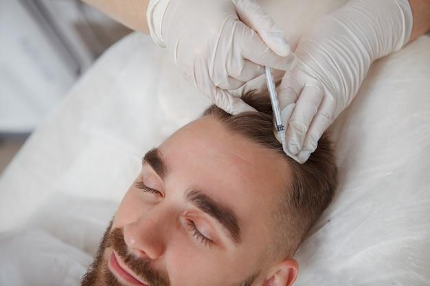 Geschnittene nahaufnahme eines jungen attraktiven mannes, der haarausfallinjektionsbehandlung durch professionelle kosmetikerin erhält