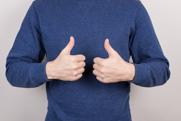 Geschnittene nahaufnahme selbstbewusster chefstudententrainer, der führung unter verwendung der hände ausdrückt, die zwei finger aufgeben, die formelle blaue pullover isolierte graue wand tragen