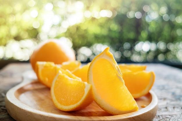 Geschnittene orange auf hölzerner platte. frische saftige frucht im sommer