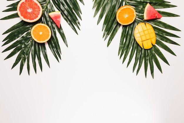 Geschnittene orange mango der reifen roten wassermelone am palmblatt