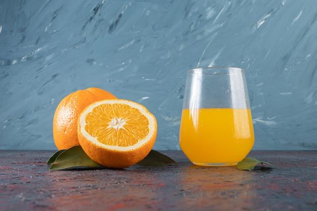 Geschnittene orange und ein glas saft auf dem gemischten tisch.