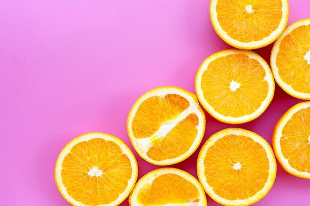 Geschnittene orangen auf rosa. hoher vitamin c, saftig und süß.