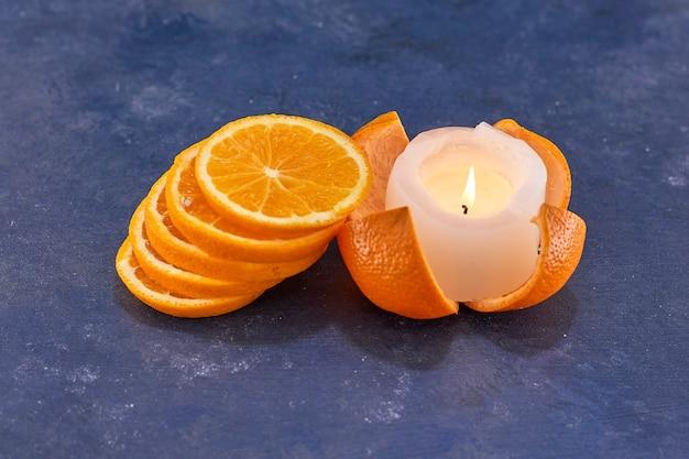 Geschnittene orangen in einem stapel auf blau mit einer brennenden kerze beiseite