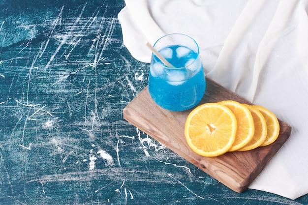 Geschnittene orangen mit einer tasse getränk auf blau.