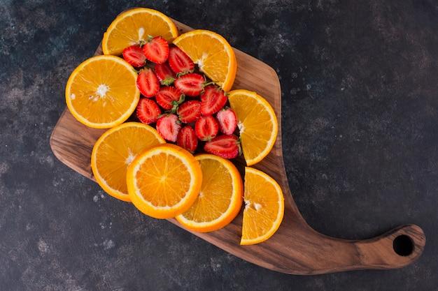 Geschnittene orangen und erdbeeren auf einem holzbrett, draufsicht