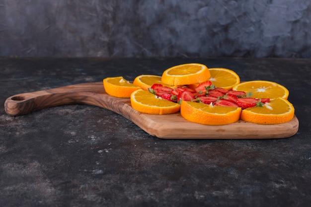 Geschnittene orangen und erdbeeren auf einem holzbrett