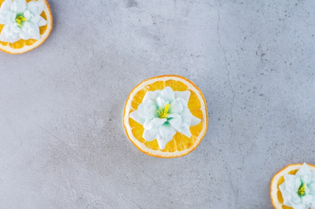 Geschnittene orangenfrucht mit weißen blüten auf grau