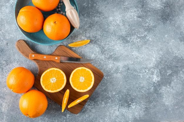 Geschnittene orangenfrüchte mit ganzen orangen auf einem holzbrett.