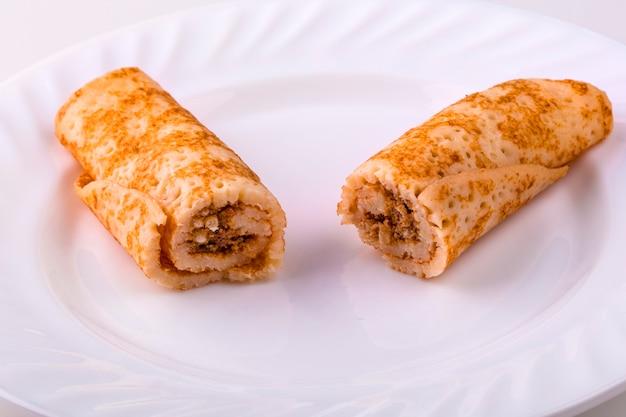 Geschnittene pfannkuchen mit leber auf einem weißen teller