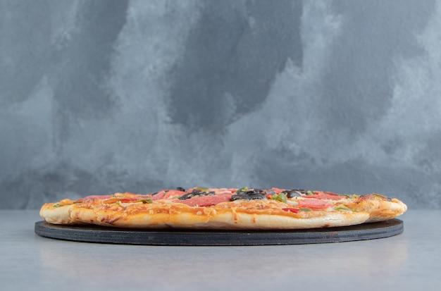 Geschnittene pizza auf einer tafel auf marmor