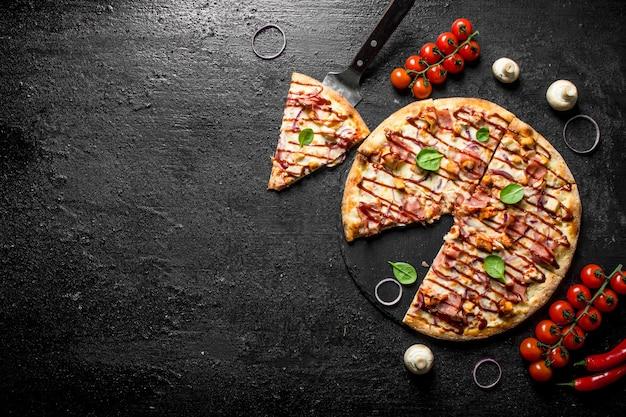 Geschnittene pizza mit huhn, speck und soße auf schwarzem rustikalem tisch.